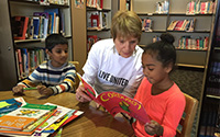 United Way volunteer reading to children